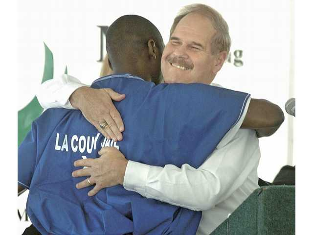 Co-founder of Hollywood Impact Studios Gary Hall, right, hugs a MERIT program graduate as he receives a movie industry scholarship at Pitchess Detention Center on Thursday.