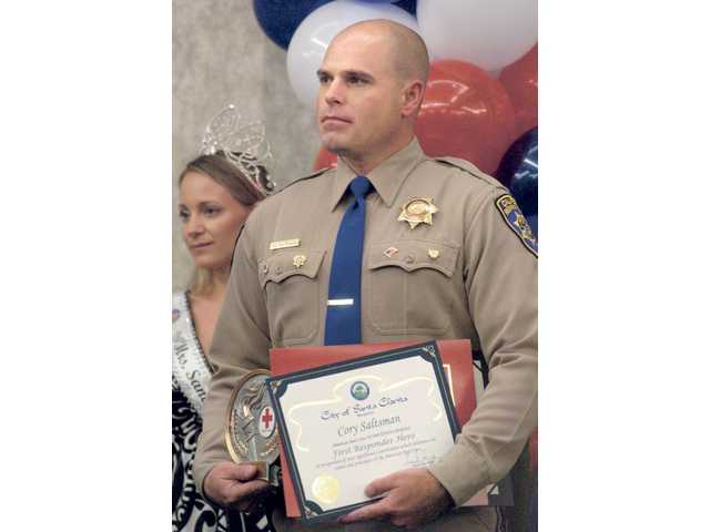 CHP Officer Cory Saltsman receives his 2009 Hometown Hero Award as First Responder Hero at a breakfast held at the Hyatt on Friday.