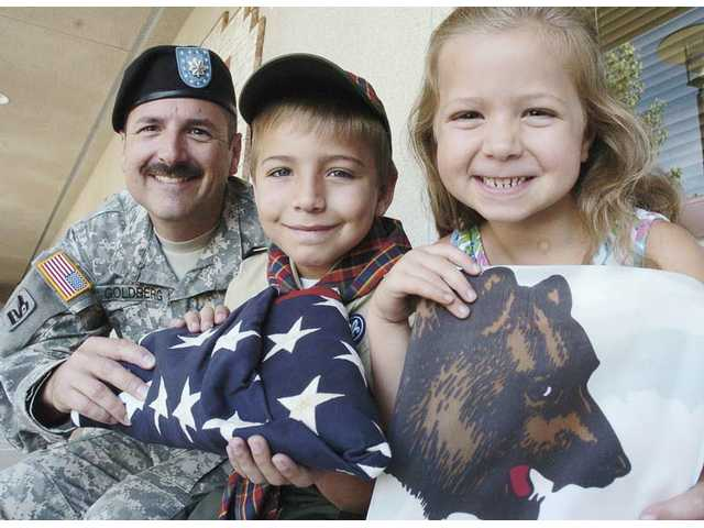 Lt. Colonel Seth Goldberg, left, donated an American and California flag that flew over the headquarters where he served in Iraq. His children Ethan, 9, center, and Gabriella, 6, hold the flags that were presented to Tesoro Del Valle Elementary School with certificates of authenticity on Friday.