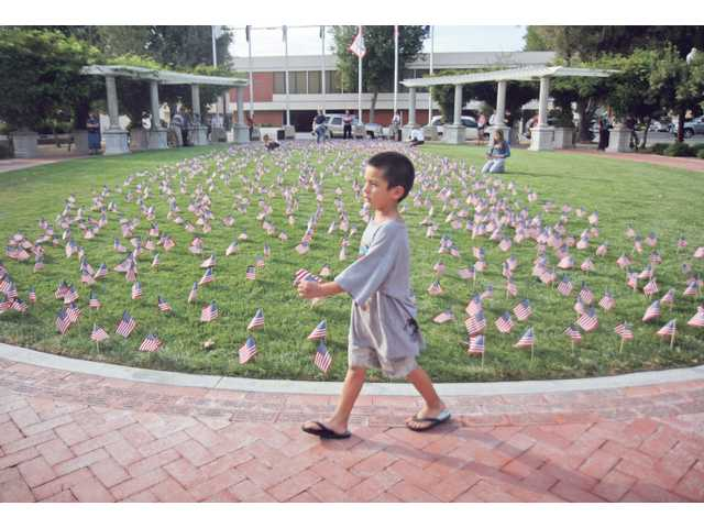 Six-year-old Nathaniel Valdes, walks past flags at the Newhall Veterans Memorial Park. He and other local kids helped place 2, 974 placed in the ground to represent each person who lost their lives in the 2001 September 11 attacks. The event was hosted by the SCV Young Republicans group.