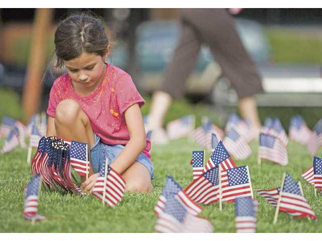 "Eight-year-old Victoria Valdes helps place flags at the Newhall Veterans Memorial Park for ""2,974 Reasons to Never Forget"" event hosted by the SCV Young Republicans on Friday afternoon. The flags will be on display for 24 hours."