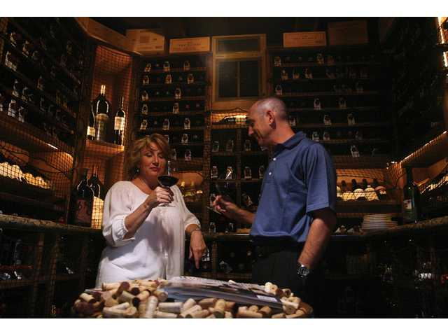 Annie and Robert Schwartz sip wine inside the wine cellar they had built in their Stevenson Ranch home.