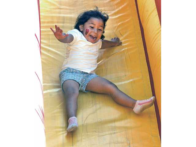Claudia Rodriguez, 3, enjoys the inflatable slide at the Day for Kids, presented by the Boys & Girls Club of SCV and the city of Santa Clarita, at Newhall Park on Saturday. Fifty-two vendors participated in the free event.