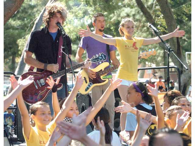 "Ally Foster, 12, right and her Elite Dance Studios class-mates dance with the band ""Letters to the Editor"" as they perform to their original composition ""The Day For Kids Theme"" at the Boys & Girls Club Day for Kids Event at Newhall Park on Saturday."
