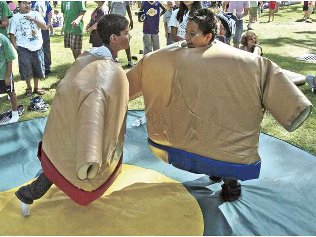 Kevin Solorio, 9, left, and Jimmy Recinos, 12, do battle as they wear padded sumo wrestler suits at the Day For Kids at Newhall Park on Saturday. More than 5,000 children and parents attended the free event.