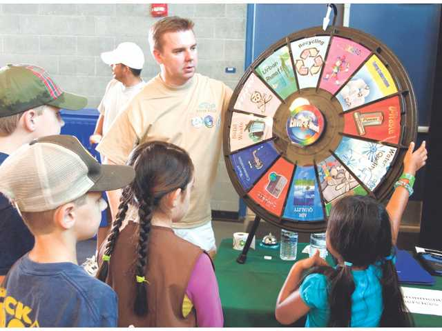 "City of Santa Clarita Environmental Analyst, Oliver Cramer, uses the ""Envir-O-Wheel"" at the exhibition following the River Rally to inspire some of the kids who participated in the event"