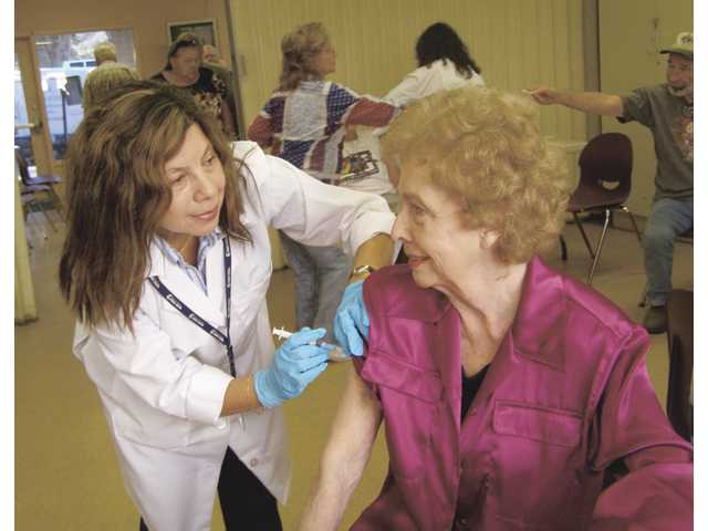 Los Angeles County Public Health Nurse Ana Garcia administers a flu shot to Jo Anne Darcy, former mayor, city councilwoman and longtime SCVSC advocate, during the November 2008 flu shot clinic held at the Senior Center. Presented through the County of Los Angeles Dept. of Public Health, the upcoming Oct. 2 outreach clinic at the Senior Center will provide free vaccines against the seasonal flu - not the H1N1 (swine) flu.