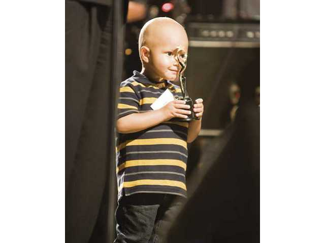 "Evan Gabor, 2, smiles to the crowd after receiving his ""Shining Star"" award."