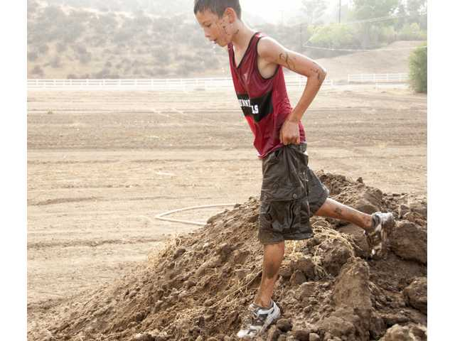 Patrick Larkin, 11, Simi Valley Running Rebel, crests the final mud hill before he takes first place in the one-mile kid run.