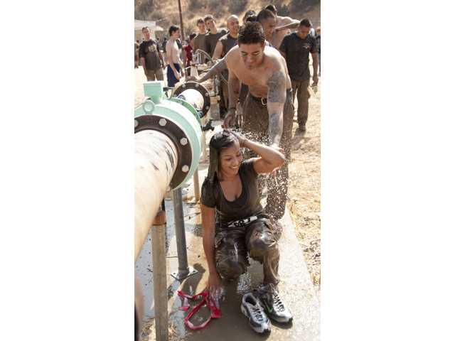 Salene Limon, 29, of Duarte, rinses off after completing a 5-mile obstacle run at the Mud Run on Sunday. The event was sponsored by the Los Angeles Sheriff's Athletic Association.