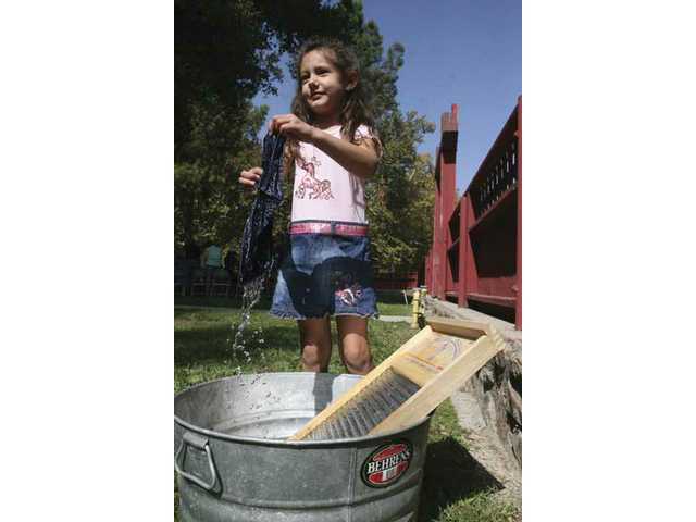 Crystal Nunez, 4, from Tujunga, gives the laundry a good scrubbing on an old-fashioned wash board during the Saturday morning ranch event at William S. Hart Museum Ranch house.