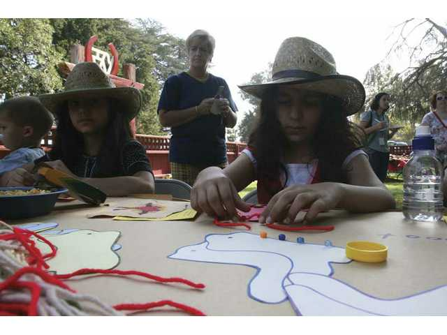 Sisters Siron, 9, left, and Garnier Mani, 10, work on arts and crafts projects. Saturday's ranch event at the Hart Museum ranch house brought about 30 families out to play cowboy style.