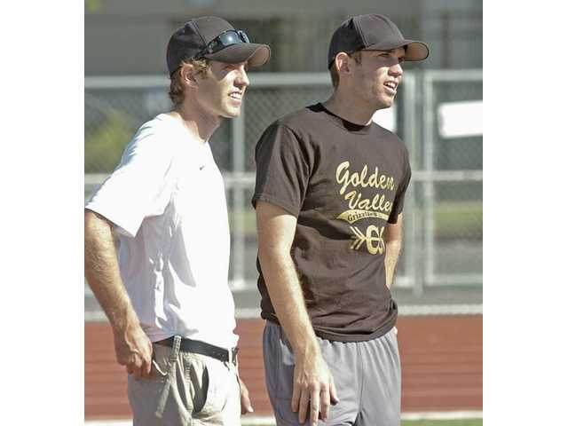 Golden Valley cross country co-head coaches Chris, left, and Rob Evans instruct their runners at practice Wednesday at Golden Valley. The Grizzlies' boys team finished 11th in the state last season and hopes for a return trip.