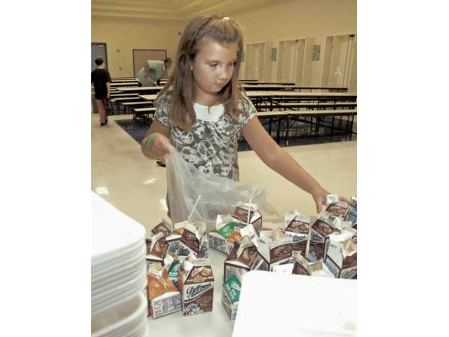 Golden Oak Community School third-grader Molly Root puts wax milk cartons and Styrofoam trays in a bag after her classmates separated them from their trash after lunch on Wednesday.