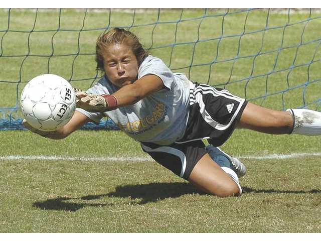 College of the Canyons goalie Carolina Dozal makes a diving save at practice Thursday on the COC campus. Like the other programs at the school, the women's soccer team is aiming for a WSC title.