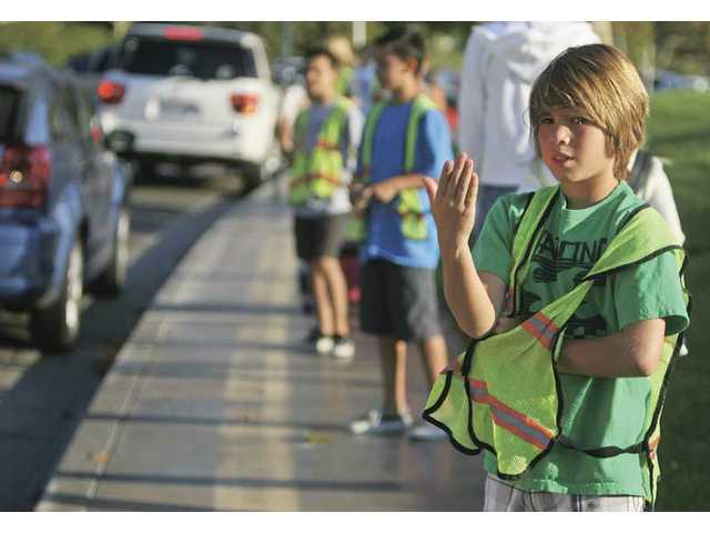 Helmers Elementary School's sixth-grader Christian Fontal helps keep traffic flowing outside his school Aug. 31. Fontal and numerous other student volunteers help alleviate morning traffic with the school's valet program. They also escort kindergartners and first-graders to class which keeps parents from getting out of their cars.