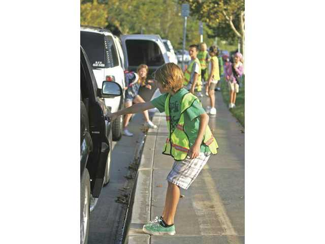 Helmers Elementary School's sixth-grade student Christian Fontal helps open a door in the valet line outside the school Aug. 31. The school has been using the valet system for seven years and has aided with the flow of traffic as parents drop off their children.