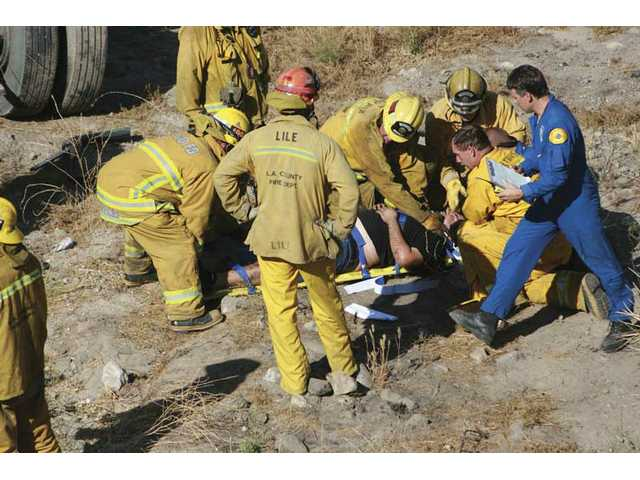 Firefighters treat an unidentified man injured Tuesday when a big-rig slammed into a SUV and went off an embankment on Highway 14 in Agua Dulce.