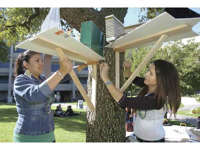 Architecture students Talia Lemus, left, and Elena Triebel hang their scale model of Las Vegas to a tree in the main commons area at College of the Canyons.