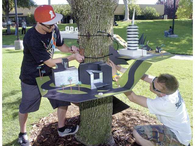 Architecture students Nick Nolan, left, and Trent Vigil hang their multi-level scale model of Hollywood to a tree in the main commons area at College of the Canyons on Wednesday.