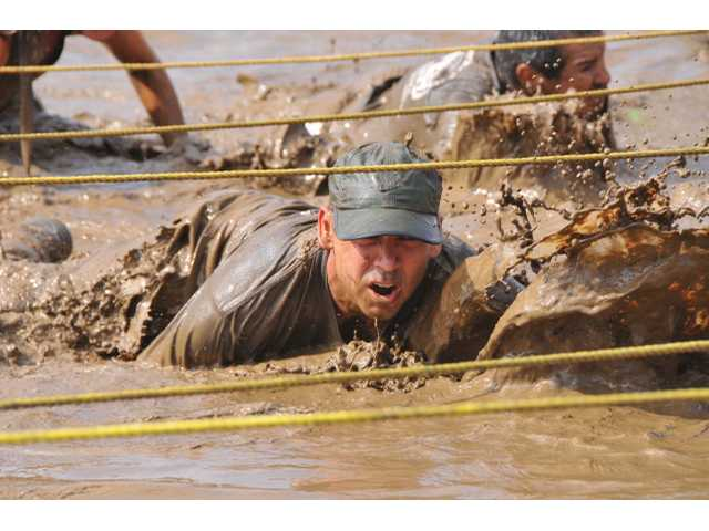 Mark Schoelen crawls through the last part of the course at the 14th Annual Mud Run at Pitchess Detention Center in Castaic on Sunday.