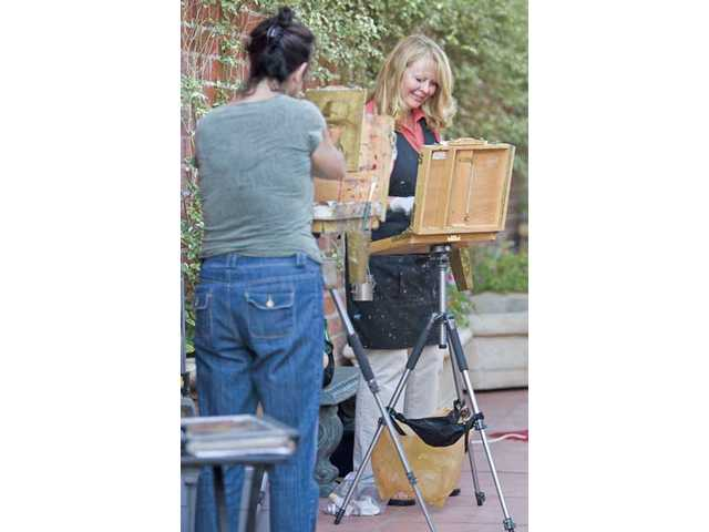 Laura Wambsgans, right, and Lorelle Miller paint portraits outside the Canyon Theatre Guild in Downtown Newhall during the first Art Walk event Thursday.