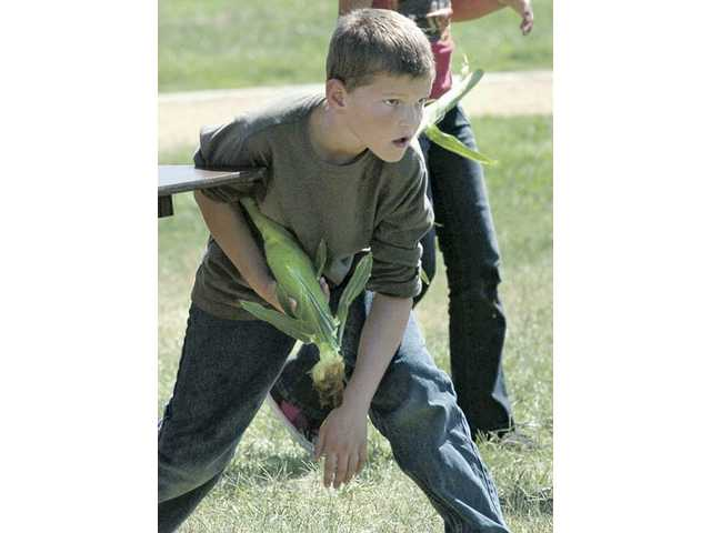 Mint Canyon Elementary School fifth-grader James Spencer waits to run in a fresh ear of corn to shuck as his class competes against fourth- and sixth-graders to shuck the most corn for the school's upcoming movie night.