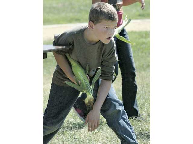 Mint Canyon Elementary School fifth-grader James Spencer waits to run in a fresh ear of corn for schucking as his class competes against fourth and fifth graders to shcuck the most corn for the school's upcoming movie night.