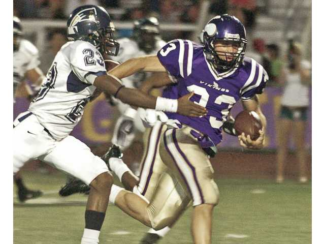 Valencia running back Steven Manfro, right, breaks a tackle by Birmingham's Kenny Pool Thursday at Valencia High. The run set up the Vikings' second touchdown of the night. Valencia went on to win 56-31.