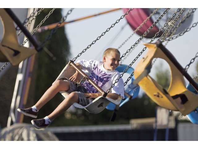 Robert Sarno, fifth-grader at Our Lady of Perpetual Help, rides the swings during the carnival. The event continue held today from 4 p.m. to 11 p.m. and Sunday from 11 a.m. to 8 p.m.