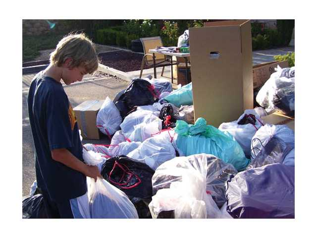 Volunteers dropped off bags of shirts, pants and jackets during the Life Teen's clothing drive for the St. Vincent de Paul Society in Los Angeles. By the end of the weekend, 10,000 pounds of clothing were collected.