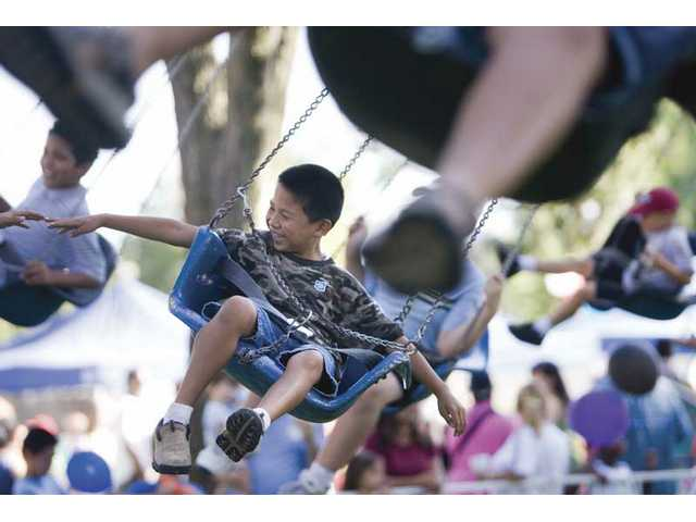 Cary Caruso, 8, rides the flying swings with his friends during the Day for Kids carnival on Saturday afternoon, at Newhall Park.