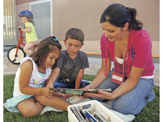 Student teacher Nancy Sandoval reads with Gaby Espinoza and Nicholas Diaz on Friday morning at the Early Childhood Education Center in the Canyon Country COC campus. Sandoval is in her second year of studying to become a preschool teacher.