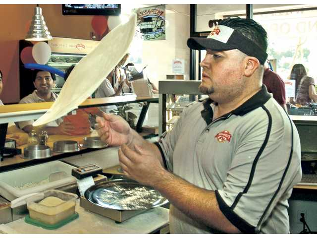 Chef Miguel Rodriguez hand-tosses pizza dough for the clients at the grand opening of Nick-N-Willy's Pizza in Valencia on Saturday.