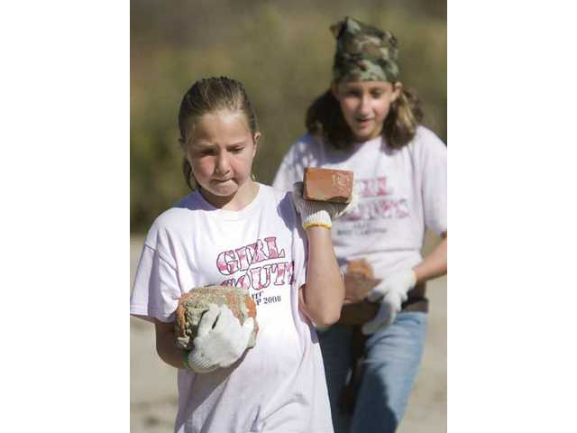 Kenney Davis, 10, carries bricks she and fellow Girl Scout Troop 368 member Audrey McIntosh, 10, found while cleaning up the Santa Clara River on Saturday during the 14th Annual River Rally.