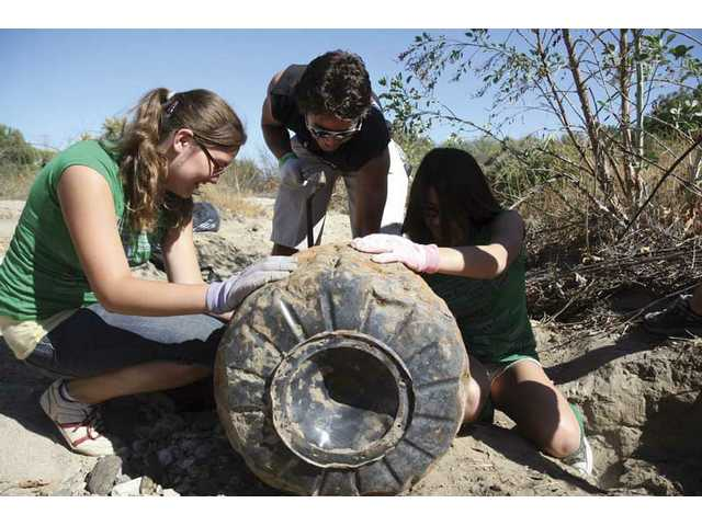 After digging a metal rim for about 40 minutes, Kelsey Taylor, 12, Joey Alderman, 17, and Katy Adelman, 12, clean the dirt off it during the 14th annual River Rally on Saturday morning.