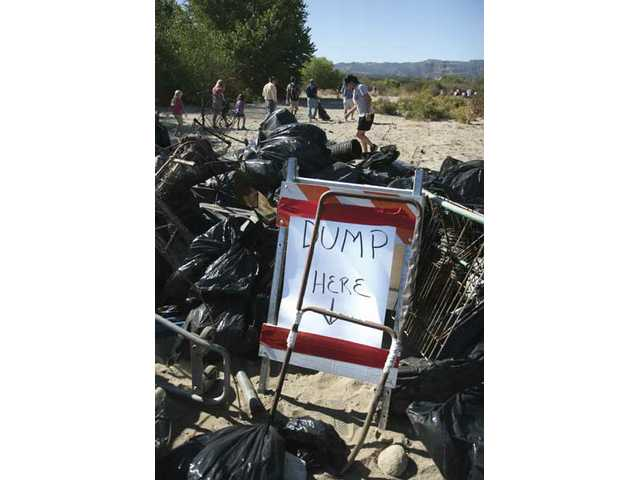 Volunteers make their way around a pile of trash collected inside the Santa Clara River during the 14th Annual River Rally.