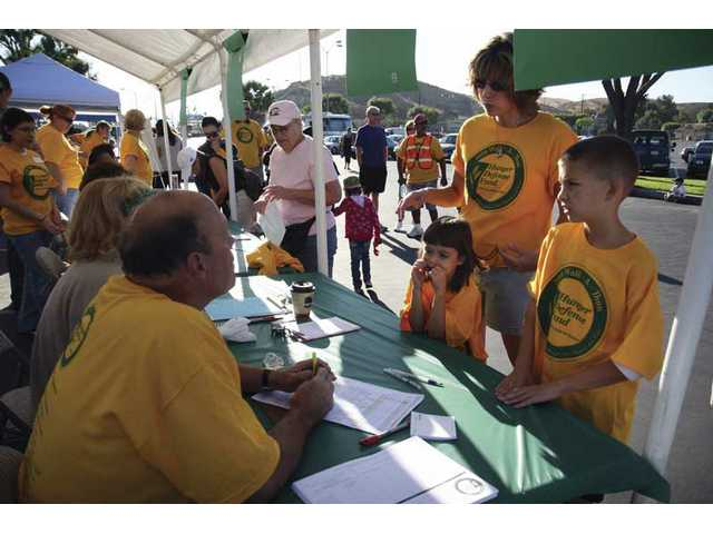 Stacey Henderson, and her children Kenna,7, and Jeremy, 10, register with Dr. William Hilton, senior pastor, from Fellowship Christina Church, to participate in the walk which benefited the Hunger Defense Fund organization, in the Kmart parking lot in Valencia on Saturday morning.
