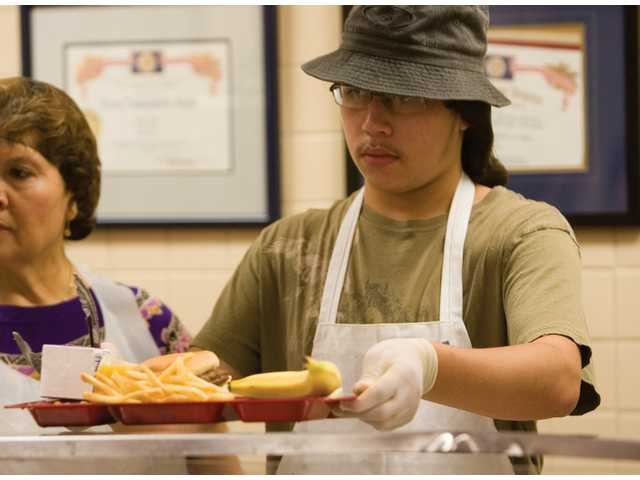 Ian Gomez, 18, from Newhall, passes out lunch at the Senior Center.