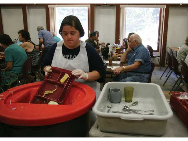 Emma Waschak, 21, from Valencia, helps clear food trays at the SCV Senior Center on Wednesday afternoon. She and several other students volunteer twice a week through the Hart district's Transitional Learning Charter.