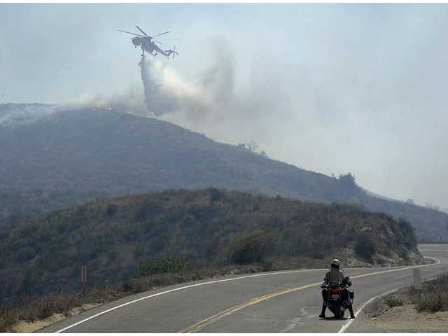 A Ventura County Sheriff deputy watches from his motorcycle as a helicopter makes a water drop on a wildfire burning in the hills of Moorpark, Calif., Tuesday, Sept. 22, 2009.