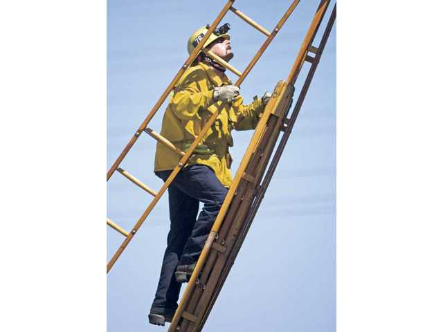 Firefighter Andrew Ahten, from Station 76 in Valencia, carries part of the ladder up another during a training session on a vacant lot on Creekside Road in Valencia on Monday morning.