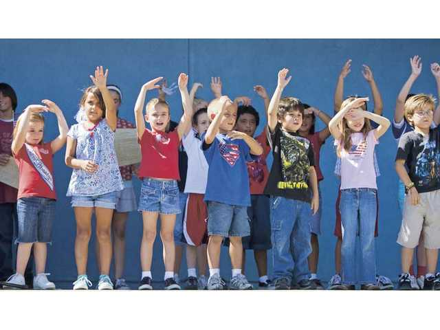 """Mitchell Elementary School second-graders sing and sign to """"God Bless America"""" during a school assembly celebrating Constitution Day on Wednesday afternoon. Student council put together the event."""