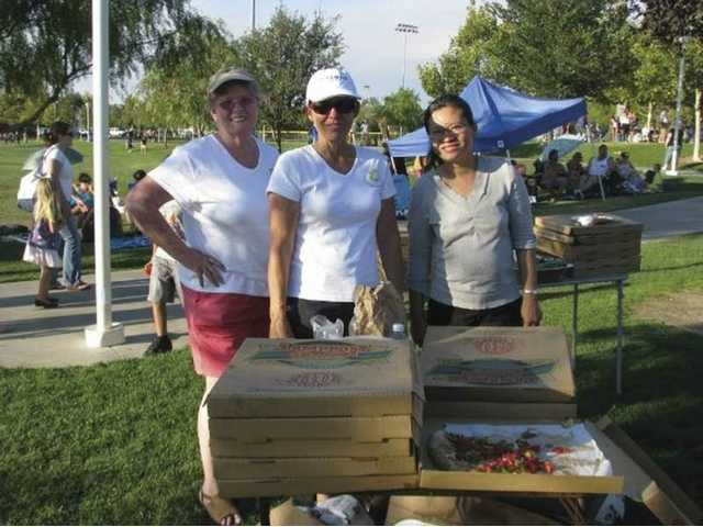 Terri Wahl-Fobre, DaAnne Smith, and Ampaipan Tan of Single Mother's Outreach serve up pizza during an outing to Concerts in the Park. The nonprofit serves approximately 100 single parent families in the Santa Clarita Valley.