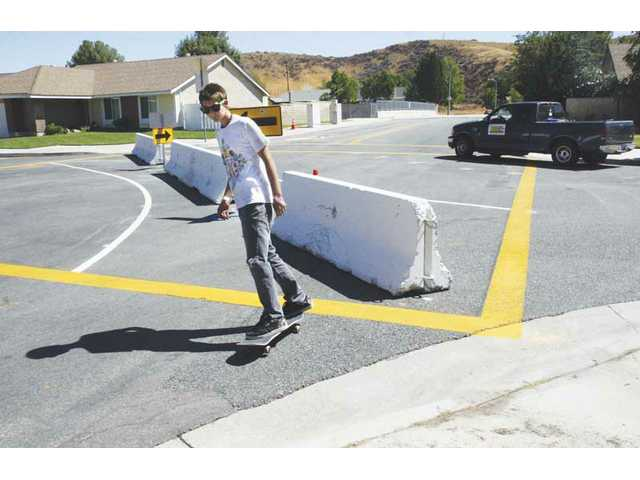 Fifteen-year-old Kevin Conway skates around a barricade, placed by the city in the middle of Benz Road and Alaminos Drive in Saugus on Wednesday afternoon.