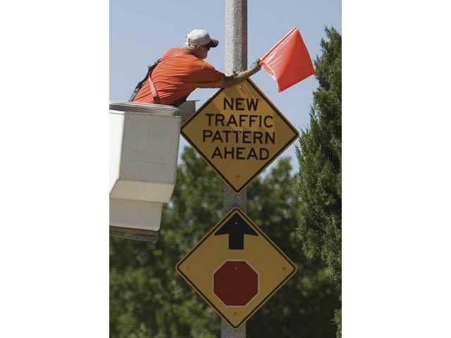 A city worker places on a light post a new sign warning drivers regarding the barricade placed in the intersection of Benz Road and Alaminos Drive in Saugus on Wednesday afternoon.