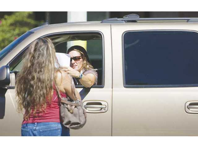 Marivic Francis hands driver Tracy Hild information about the negatives of the barricade placed by the city on the corner of Benz Road and Alaminos Drive in Saugus.