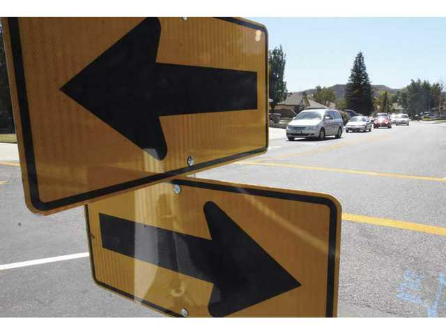 Arrows point cars into a new traffic pattern because of barricades placed in the middle of Alaminos Drive and Benz Road in Saugus on Wednesday afternoon.