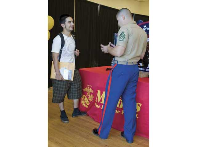 Staff Sgt. Career Recruiter Jose Medrano, right, discusses Marine Corps opportunities with Raul Hernandez, of Sylmar, at the College of the Canyons Job & Career Fair on Wednesday.