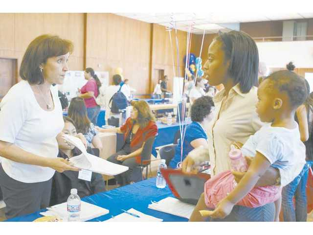 Tia Baker, right, of Santa Clarita, talks with Aurea Jester, left, about job opportunities with the California State Board of Equalization at the College of the Canyons Job & Career Fair Wednesday.